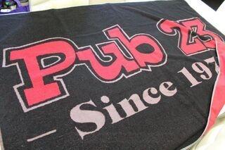 Kudottu logolla pyyheliine Pub23